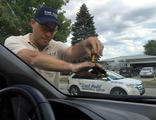 windshield repair technician repairing chip on windshield.